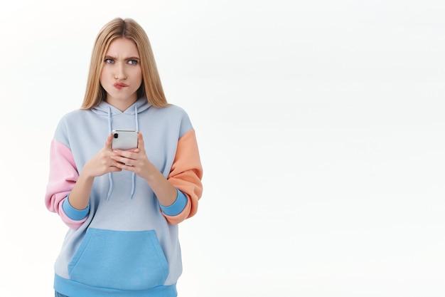 Koncepcja komunikacji, technologii i online. zakłopotana i zamyślona młoda blond dziewczyna myśli, jak odpowiedzieć na ryzykowny tekst w aplikacji randkowej