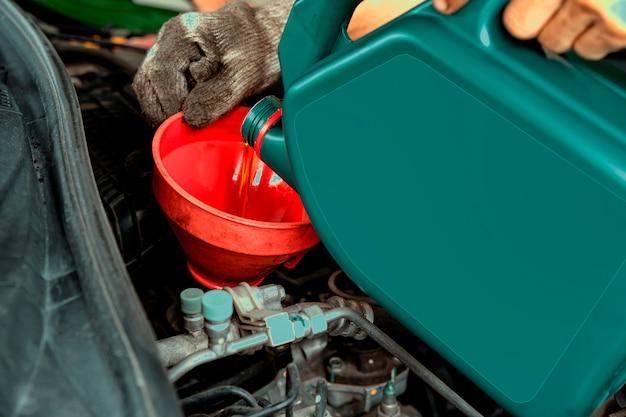 Koncepcja konserwacji samochodu. mechanik samochodowy wymienia i wlewa świeży olej do silnika na stacji serwisowej. technik naprawy samochodów wlewa nowy olej silnikowy, aby wymienić stary