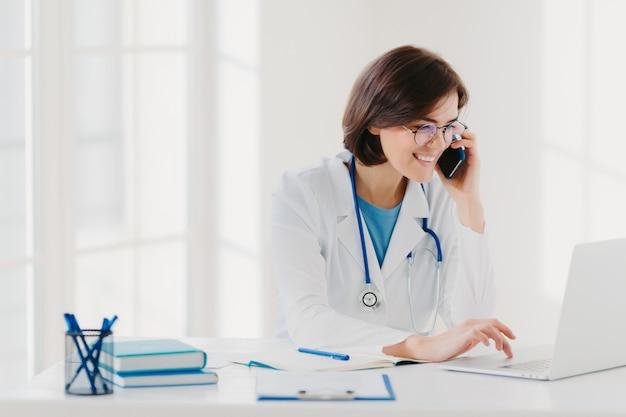 Koncepcja konsultacji online. rozochocony żeński medyczny pracownik opowiada przez komórkowego