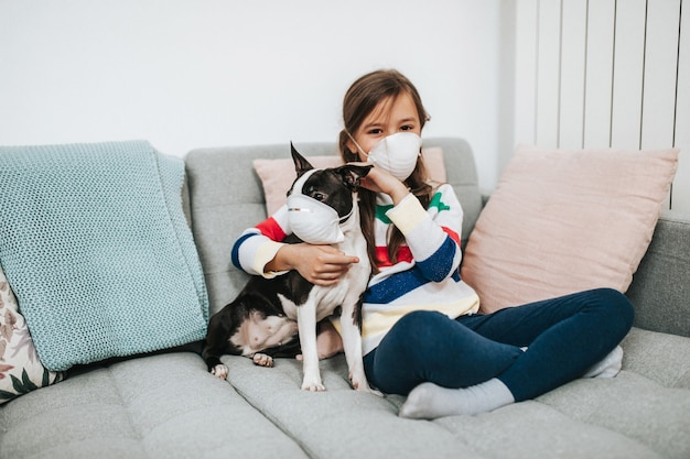 Koncepcja koronawirusa covid-19. dziewczyna i jej pies z maskami ochronnymi na twarzach bawią się w życie podczas kwarantanny.