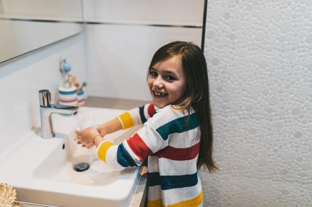 Koncepcja koronawirusa covid-19. dziewczyna myje ręce w łazience mydłem antybakteryjnym.
