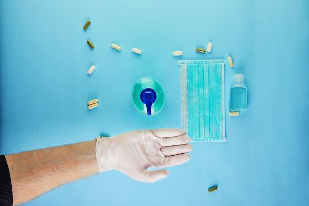 Koncepcja koronawirusa covid-19, jak uchronić się przed infekcją. włożyć rękawicę ochronną i żel dezynfekujący, maskę i pigułki.