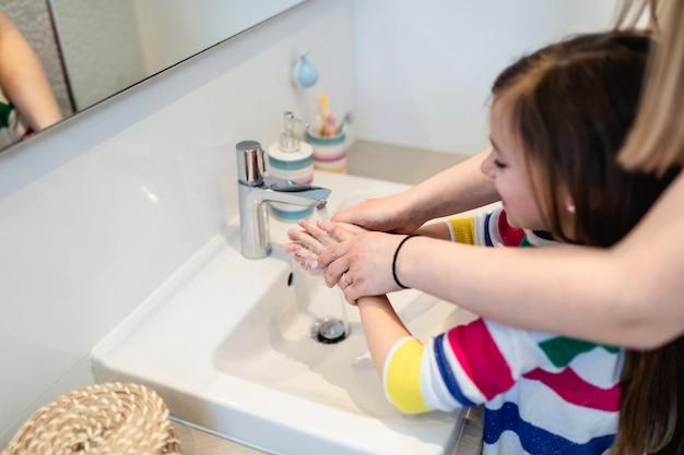 Koncepcja koronawirusa covid-19. matka i córka myją ręce w łazience mydłem antybakteryjnym.