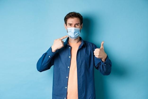 Koncepcja koronawirusa i pandemii. młody zdrowy mężczyzna, wskazując na maskę medyczną i pokazując kciuki do góry, stosując środki zapobiegawcze przed łapaniem covid-19, niebieskie tło.