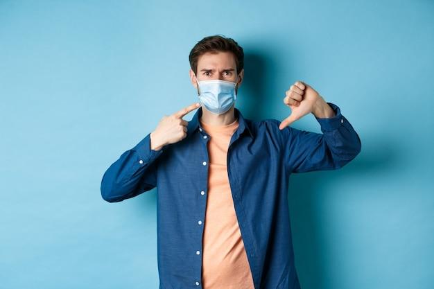 Koncepcja koronawirusa i pandemii. rozczarowany młody człowiek wskazujący na maskę medyczną i pokazujący kciuk w dół, dezaprobata i niechęć do zasad kwarantanny, niebieskie tło.