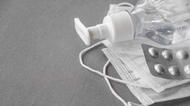 Koncepcja koronawirusa: medyczna maska ochronna, antyseptyki i pigułki na szarym tle. przestrzeń tekstowa