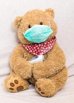 Koncepcja koronawirusa: miś z maską medyczną przytrzymuje termometr na czoło na podczerwień (pistolet z termometrem)