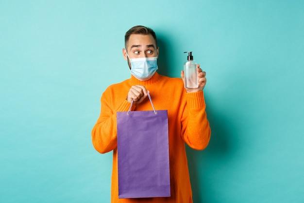 Koncepcja koronawirusa, pandemii i stylu życia. mężczyzna w masce pokazano torbę na zakupy i rękę