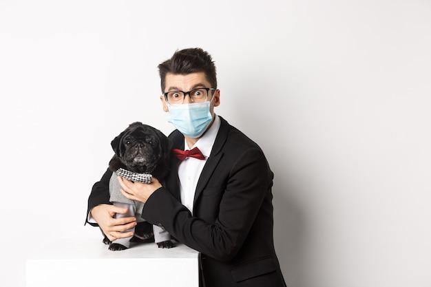 Koncepcja koronawirusa, zwierząt domowych i uroczystości. szczęśliwy właściciel psa w garniturze i masce na twarz, przytulający słodkiego czarnego mopsa w kostiumie, stojący na białym tle