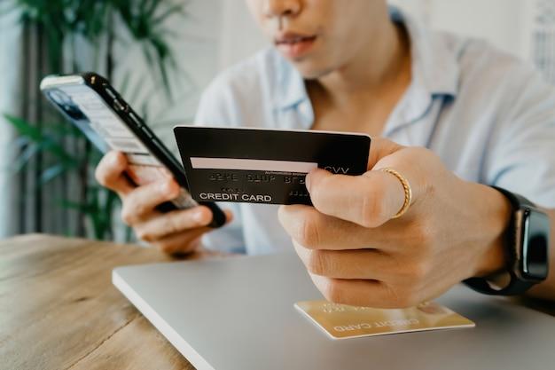 Koncepcja korzystania z karty kredytowej na zakupy online mężczyzna posiadający smartfon i wprowadzanie danych karty kredytowej.