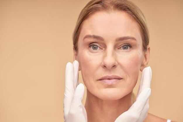 Koncepcja kosmetologii i pielęgnacji skóry kosmetyczka ręce w białych rękawiczkach sprawdzająca wcześniej kobiecą skórę twarzy