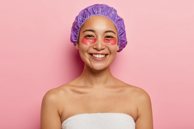 Koncepcja kosmetologii i pielęgnacji skóry. wesoła azjatka uśmiecha się pozytywnie, nakłada hydrożelowe plastry pod oczy, nosi czepek kąpielowy, stoi bez koszuli, owinięta białym ręcznikiem, odizolowana na różowej ścianie