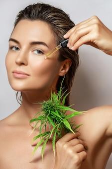 Koncepcja kosmetyków cbd. piękna kobieta z liściem konopi na szarym tle
