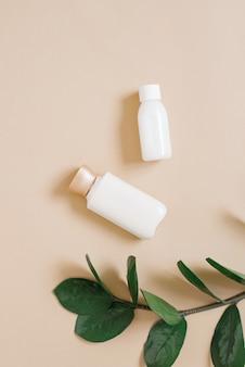 Koncepcja kosmetyków organicznych pochodzenia roślinnego. butelki z kremem do ciała lub twarzy i gałęzią rośliny tropikalnej na beżowej powierzchni