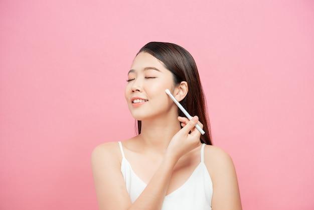 Koncepcja kosmetyków, zdrowia i urody - piękna kobieta z pędzlem do makijażu