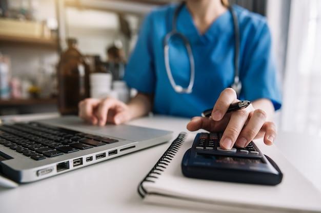 Koncepcja kosztów i opłat opieki zdrowotnej. ręka inteligentnego lekarza korzystała z kalkulatora i smartfona, tabletu do obliczania kosztów leczenia w szpitalu
