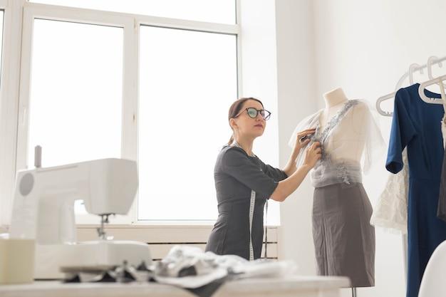 Koncepcja krawcowa, krawiec, moda i salon - widok z boku projektanta mody kobiet pomiaru materiałów na manekinie w biurze.