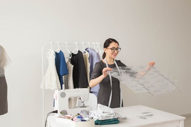 Koncepcja krawcowa, krawiecka, modowa i salonowa - portret utalentowanej krawcowej pracującej z tekstyliami do szycia ubrań.