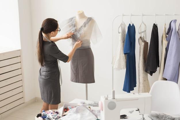 Koncepcja krawiecka, krawiecka, moda i salon - portret utalentowanej krawcowej pracującej z tekstyliami do szycia ubrań.