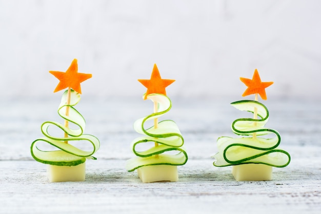 Koncepcja kreatywna ustawiła choinki z ogórkiem, serem i gwiazdą marchwi. śmieszne jedzenie dla dzieci na imprezę noworoczną na szarym tle z miejsca na kopię