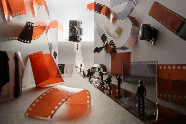 Koncepcja kreatywnego pomysłu - miniaturowi ludzie z klasycznym aparatem i filmami