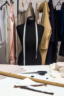 Koncepcja kreatywnego projektowania studio mody z manekina i stylowe modne modne ubrania na wieszakach, krawiectwo pracy, sklep krawiecki, szwalnia
