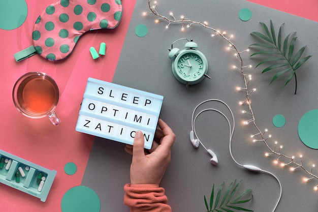 """Koncepcja kreatywnego zdrowego snu. maska do spania, budzik, słuchawki, zatyczki do uszu, herbata i pigułki. dwukolorowy różowy papier rzemieślniczy ze światłami. tekst """"optymalizacja snu w ręku."""