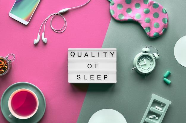 Koncepcja kreatywnego zdrowego snu. maska do spania, budzik, słuchawki, zatyczki do uszu, uspokajająca herbata i pigułki. podziel dwa odcienie na różowy i zielony