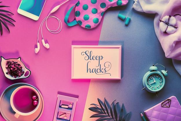 """Koncepcja kreatywnego zdrowego snu. maska do spania, słuchawki z alarmem, zatyczki do uszu, uspokajająca herbata i pigułki. dwukolorowa różowa i zielona ściana papieru podzielona liśćmi. tekst """"sleep hacks"""" w ramce."""