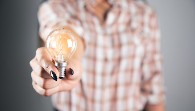 Koncepcja kreatywności pomysłów, kobieta trzyma żarówkę