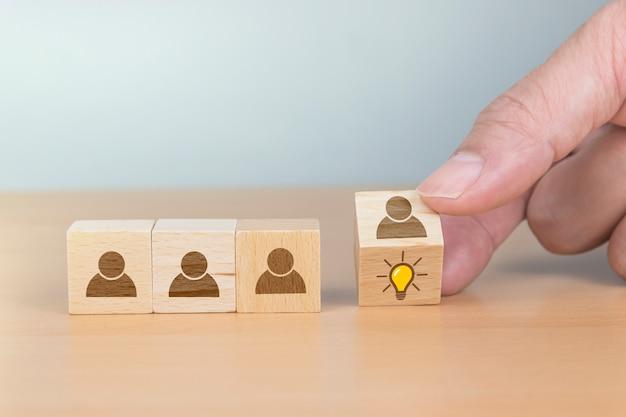Koncepcja kreatywny pomysł i innowacja. ręcznie odwróć drewniany blok kostki z ludzkim symbolem głowy i ikoną żarówki