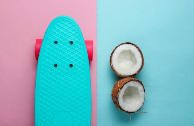 Koncepcja kreatywnych lato. deskorolka, połówki kokosa na niebieskim różowym tle. trend w pastelowych kolorach.