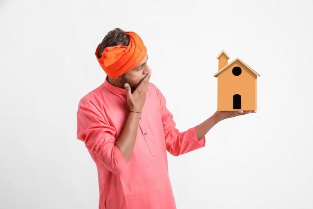 Koncepcja kredytu mieszkaniowego. indyjski mężczyzna pozowanie na białej ścianie