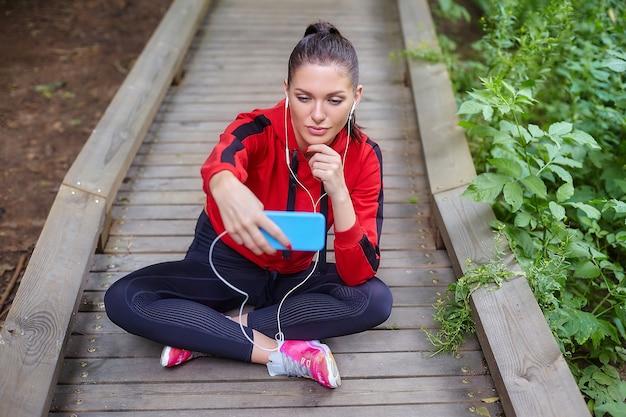 Koncepcja kształcenia na odległość. atrakcyjna dziewczyna w odzieży sportowej siedzi na drewnianej ścieżce w leśnym parku. lekcje online za pośrednictwem smartfona.