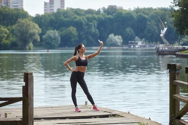Koncepcja kształcenia na odległość. atrakcyjna dziewczyna w odzieży sportowej stoi na drewnianym molo w parku miejskim. lekcje online za pośrednictwem smartfona.