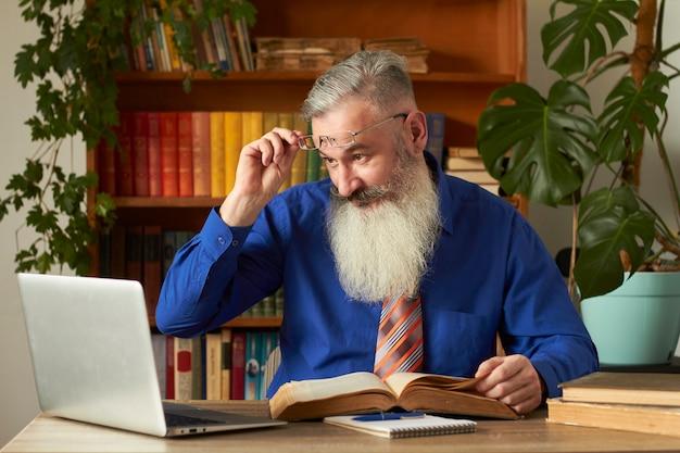 Koncepcja kształcenia na odległość. nauczyciel profesor nauczyciel uczy dyscypliny w internecie. dojrzały brodaty mężczyzna odpowiada na pytanie nauczyciela za pośrednictwem laptopa.