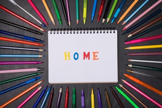 Koncepcja kształcenia w domu. pojęcie dystansu społecznego. widok z góry na zdjęcie długopisów i ołówków wokół pustego notatnika z domowym słowem wyizolowanym na tablicy