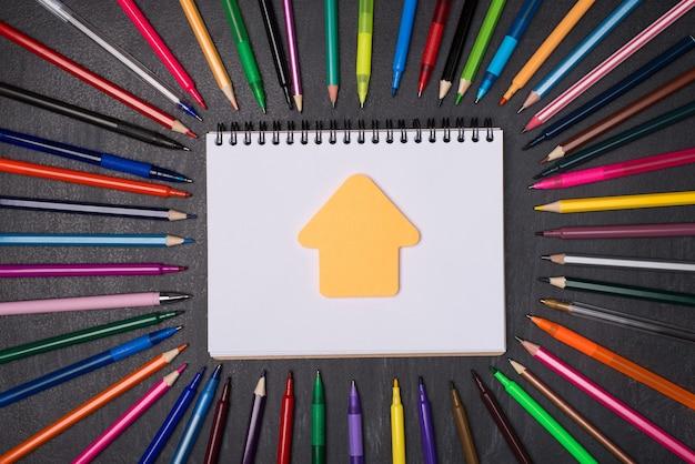 Koncepcja kształcenia w domu. widok z góry na zdjęcie długopisów i ołówków wokół pustego notatnika z notatką w kształcie domu odizolowaną na tablicy