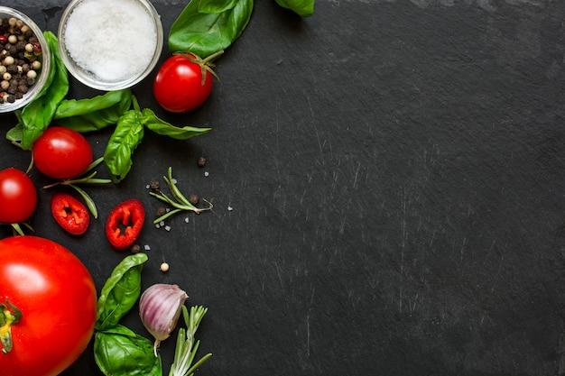 Koncepcja kucharz pracy z warzywami, przyprawami i ziołami na ciemnym tle.