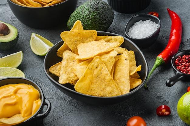Koncepcja kuchni meksykańskiej. nachos - chipsy totopos z żółtej kukurydzy z różnymi sosami, na szarym stole