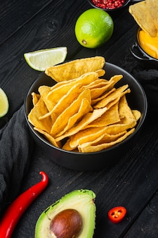 Koncepcja kuchni meksykańskiej. nachos - żółte kukurydziane chipsy totopos z różnymi sosami, na czarnym drewnianym tle