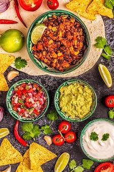 Koncepcja kuchni meksykańskiej: tortille, nachos z guacamole, salsa, chili con carne, widok z góry.
