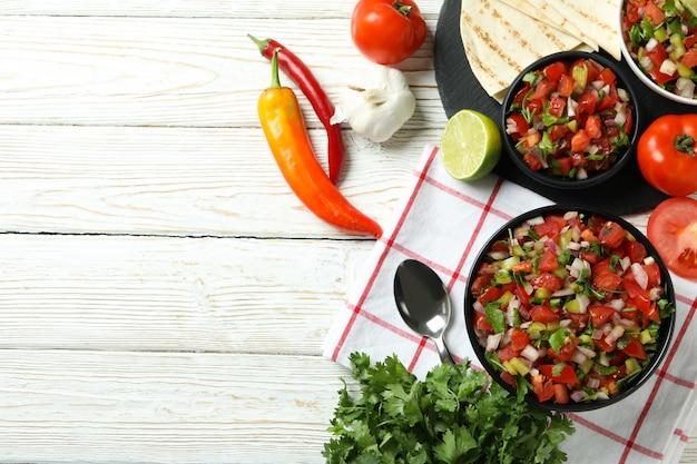 Koncepcja kuchni meksykańskiej z pico de gallo na białym drewnianym stole