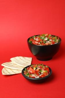 Koncepcja kuchni meksykańskiej z pico de gallo na czerwonym tle
