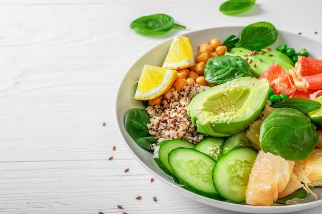Koncepcja kuchni wegańskiej: komosa ryżowa z awokado, ogórkami, zielonym groszkiem, ciecierzycą, szpinakiem i owocami cytrusowymi na białym tle.