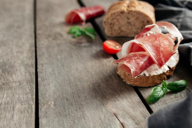 Koncepcja kuchni włoskiej. chrupiący tost z twarożkiem i cienko pokrojoną szynką, pomidorki koktajlowe