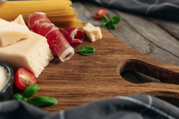 Koncepcja kuchni włoskiej. deska do krojenia, kawałki parmezanu, tarty ser, surowy makaron