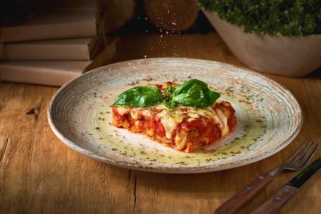 Koncepcja kuchni włoskiej. porcja smacznej pieczonej lasagne na rustykalnym drewnianym stole