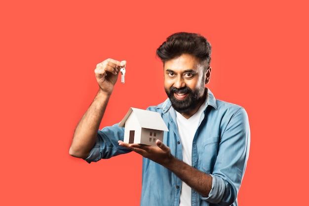 Koncepcja kupna nieruchomości i ludzie. indyjski brodaty mężczyzna z miniaturowym modelem domu, kluczami i skarbonką na czerwono