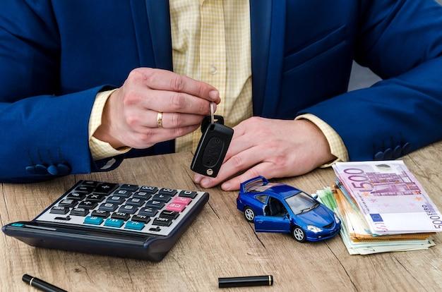 """Koncepcja """"kupowanie samochodu"""", biznesmen z modelem samochodu i pieniędzmi"""